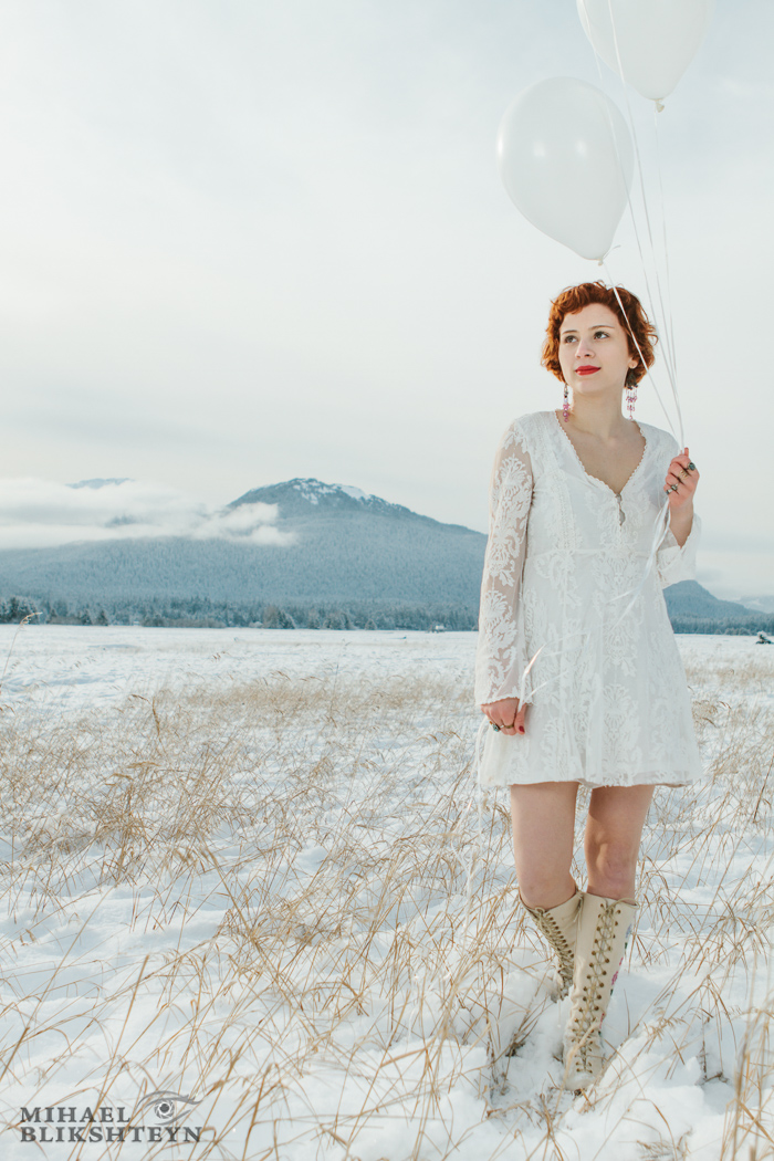 Young woman in white dress and white boots holding white balloons on a snow-covered white meadow