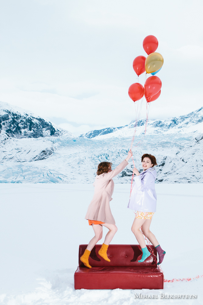 Two young women flying off a red couch on helium balloons in fro